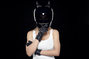 People, sports, hobby, profession, extreme and risk concept. Studio shot of young blonde woman motorcyclist in sleeveless t-shirt, black leather gloves and safety helmet, standing in confident posture Wall mural