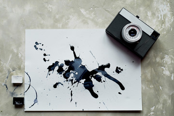 A palette of black and white paint. a sheet of white art paper with black dye ink. Old retro camera