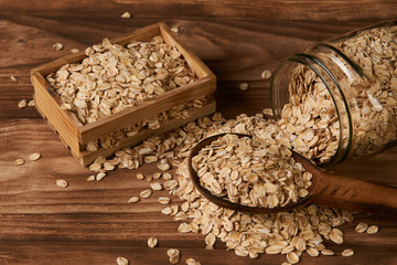 Oatmeal flakes, close-up. Dry rolled oat flakes oatmeal in a glass jar and wood box on an old wooden table background. Healthy vegetarian diet food and agriculture concept