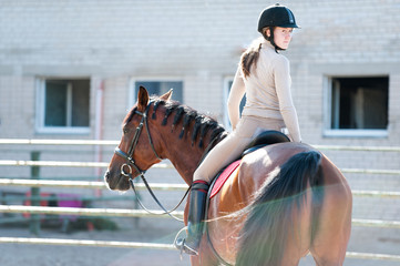 Young lady riding a horseback at equestrian farm