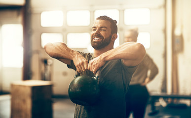 Smiling young man lifting a dumbbell while working out Wall mural