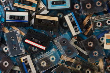 Set of old retro audio cassettes tape on blue background, close-up top view.
