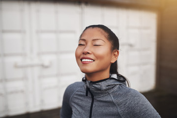 Smiling young Asian woman taking a break from her run Fotoväggar
