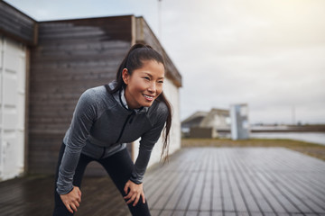 Smiling young Asian woman taking a break while out jogging Wall mural