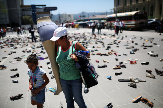 """A woman walks by an installation named """"My feet are my wings"""" to remember the victims killed during the funeral of slain Salvadorean Archbishop Oscar Arnulfo Romero during the 38th anniversary of his murder in San Salvador"""