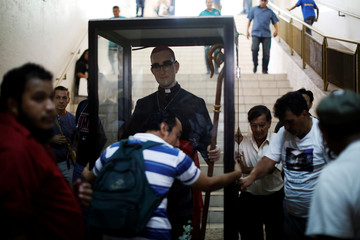 Catholic faithful transport a statue of slain Salvadorean Archbishop Oscar Arnulfo Romero during the 38th anniversary of his murder in San Salvado