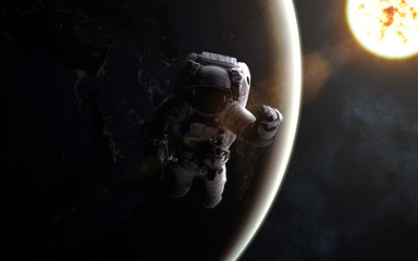 Astronaut in outer space. Sun and Earth. Image in 5K resolution for desktop wallpaper. Elements of the image are furnished by NASA