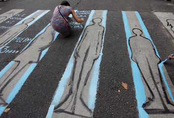 A member of a human rights group draws a silhouette that represents the disappeared during a demonstration to commemorate the 42nd anniversary of the 1976 military coup in Buenos Aires