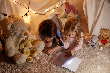 Top view of reading interested children. They lying on soft carpet in comfortable playroom. Girl holding flashlight in hand