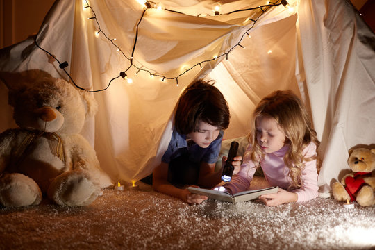 Little kids involving in reading amazing book. They lying in nice toy tent in playroom. Boy holding flashlight in hand