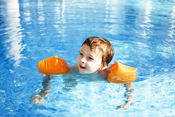 little cute real boy in swimming pool close up smiling, lifestyl