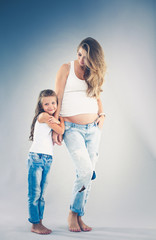 Happy child holding belly of pregnant woman. Mothers day concept