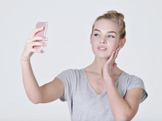Young caucasian girl makes selfies