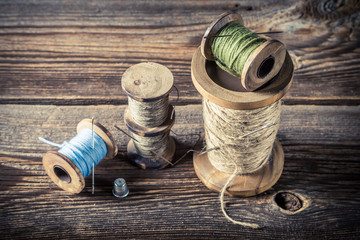 Needles and threads in tailor workshop on wooden background