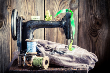 Old sewing machine with colorful threads, scissors and cloth