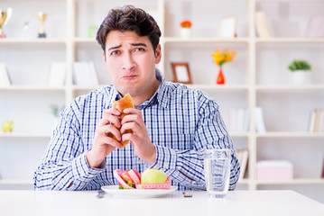 Man having dilemma between healthy food and bread in dieting con