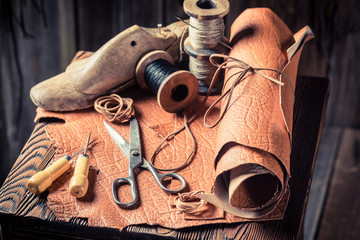 Cobbler workplace with tools, leather and threads