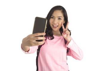 Cute tourist girl in pink t-shirt with backpack taking selfie photo.