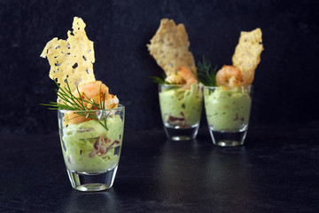 avocado cream or guacamole with shrimps and cheese crisp in a glass, appetizer or party snack on a dark slate background with copy space