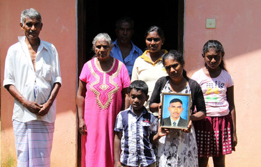 Family of H.G Kumarsinghe hold a portrait of the man whose death at the hands of three Muslim men sparked the rioting in Kandy