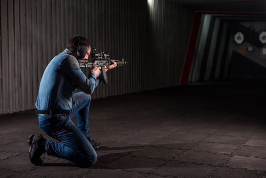 An adult man in jeans clothes, headphones and glasses, holding a Kalashnikov rifle with an optical sight. Trains fire with automatic weapons at the shooting range.