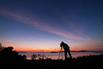 Professional photography man take a photo sunset or sunrise dramatic sky over the tropical sea in phuket thailand.