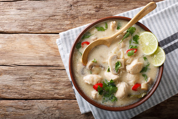 Thai chicken soup tom kha gai close-up in a bowl. horizontal top view from above