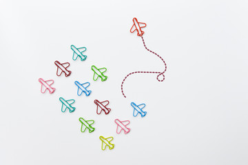 Business concept for group of plane paperclip point to one direction with another one red individual plane paperclip is point to another directi