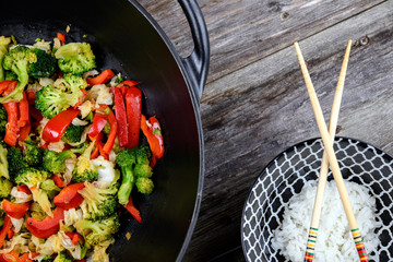 wok with vegetables, bowl of rice and chopsticks on wooden ground