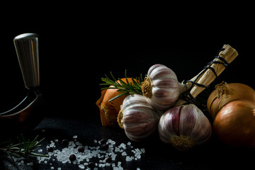 A bunch of garlic, an onion, salt and rosemary with a chopper
