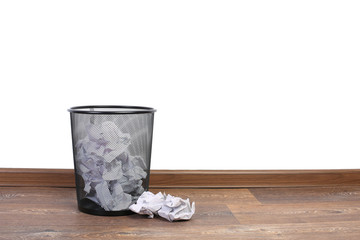 Trash can with papers on the floor