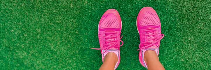 Feet selfie of pink fashion running shoes POV standing on grass of city park. Girl ready to go jogging outside walking on copy space banner background.
