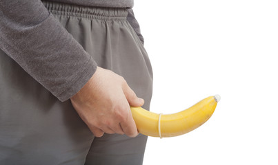 man holding banana with condom. concept of sexual protection