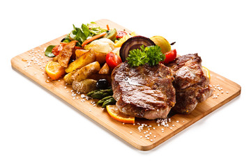 Roast steak with vegetables on cutting board