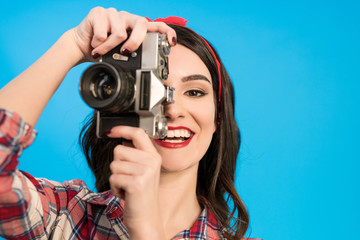 The happy woman takes a photo with an retro camera on the blue background