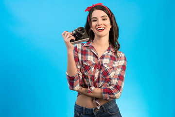 The happy woman with an retro camera standing on the blue background