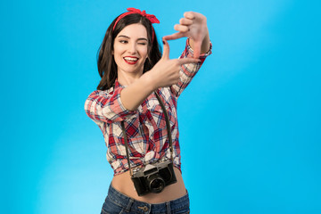 The cheerful woman with an retro camera standing on the blue background