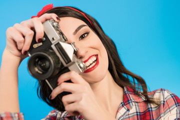 The woman takes a photo with an retro camera on the blue background