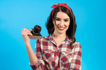 The woman with an retro camera standing on the blue background