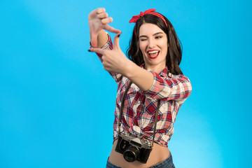 The cute woman with an retro camera gesturing on the blue background