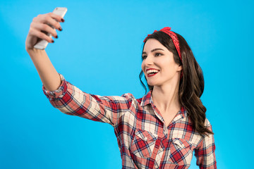 The cute woman makes a selfie on the blue background