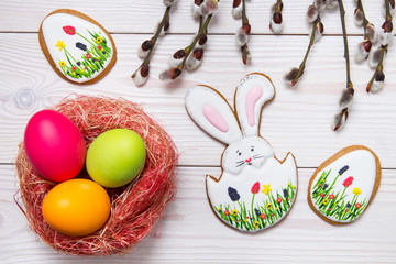 Gingerbread Easter set painted eggs and willow twig on white wooden background.  Easter Bunny and eggs, gingerbread