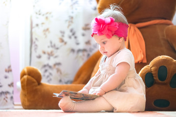 10 months old baby girl examining a book