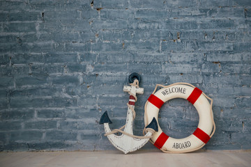 Composition on a sea theme with an anchor and life ring on a gray brick wall.