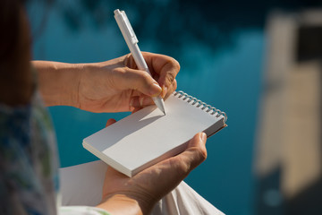Hand writing on note pad.Woman hands holding  note pad writing with white pen relaxing by the pool at sunset ,blurred background.