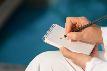 Hand writing on note pad.Woman hands holding  note pad writing with black pencil relaxing by the pool at sunset ,blurred background.