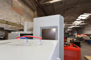 Protective transparent glasses lie on a gray surface against the background of the factory production