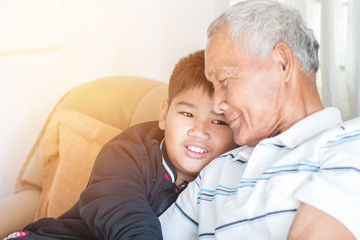 Father and Dad Day concept : Asian retired Grandfather and nephew or grandson, young boy hugging Living in house happily together, relationship between familys members is guaranteed by warm family