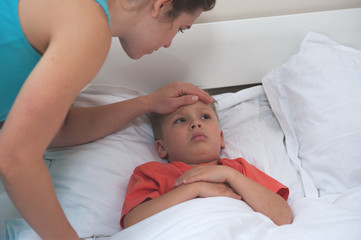 Unidentified young mother in a blue dress checks the temperature of little cute sick son sitting on the bed