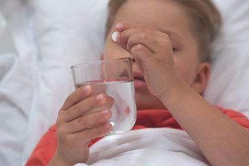 Close-up - Little sick cute cboy holding a pill and a glass of water lying on the bed